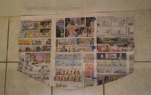 newspaper cut into a template to make a bath mat