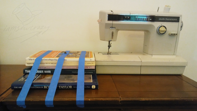 books taped to table next to sewing machine