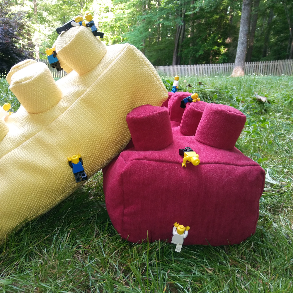 throw pillow shaped like lego brick with minifigures attached