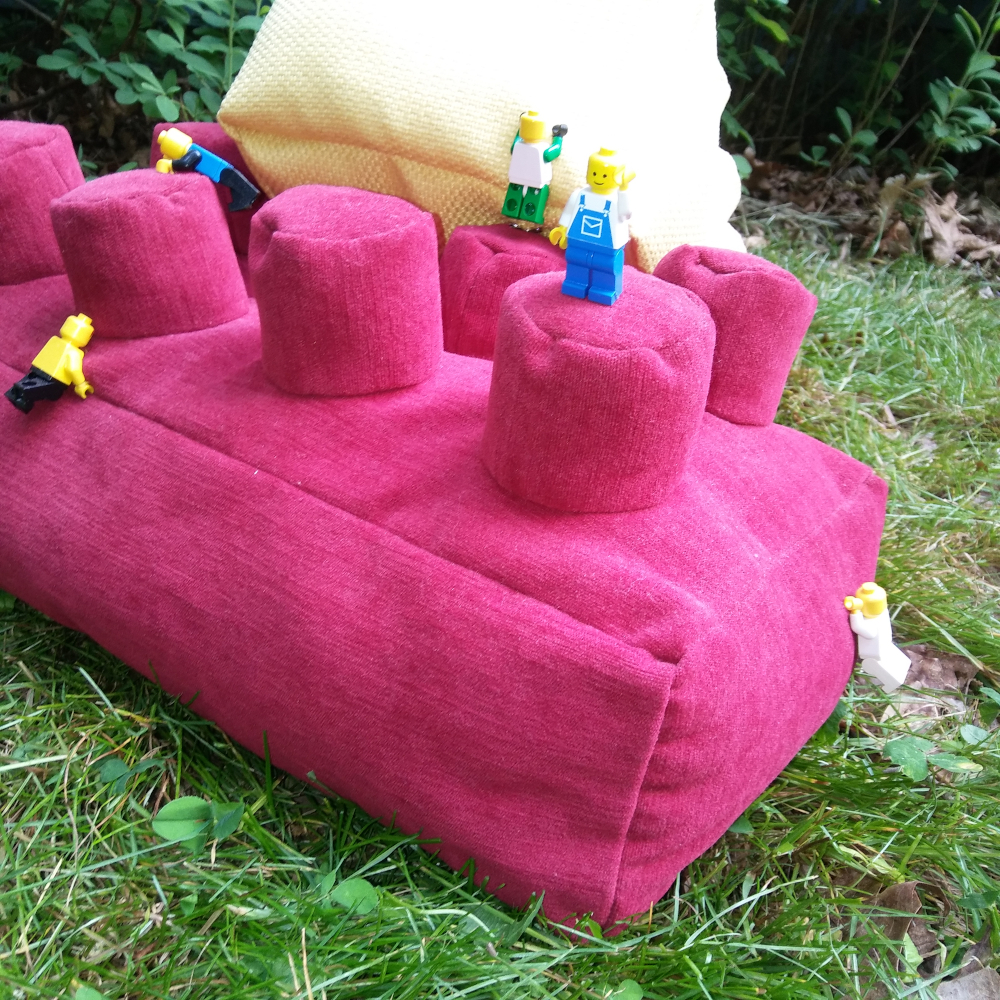 lego minifigures climbing on lego brick-shaped throw pillow