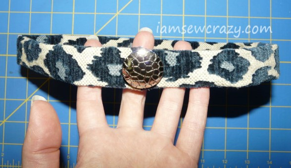 sewing a button to the hatband