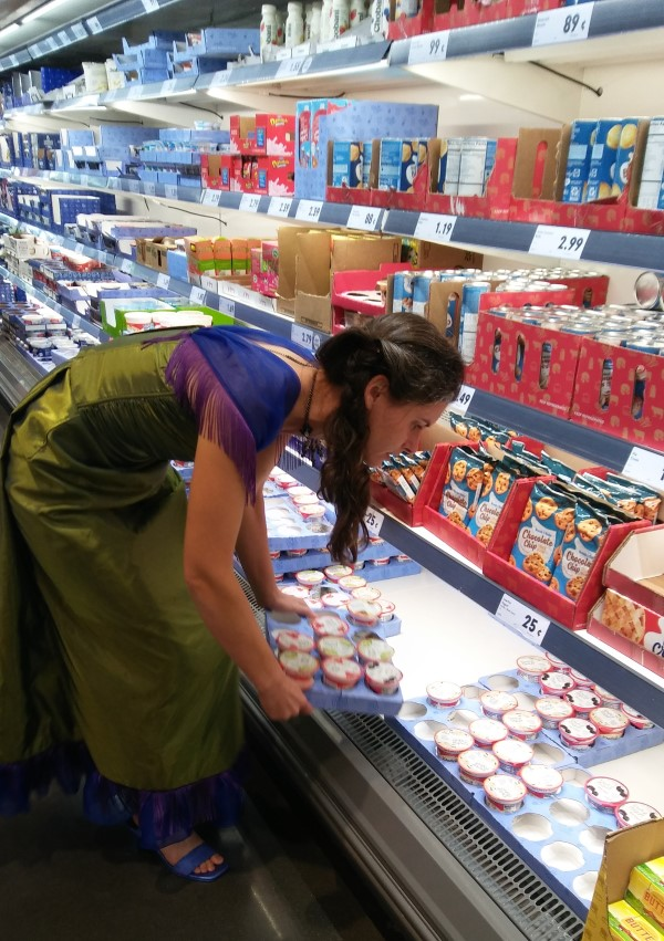 woman wearing a peacock dress in a grocery store selecting yogurt