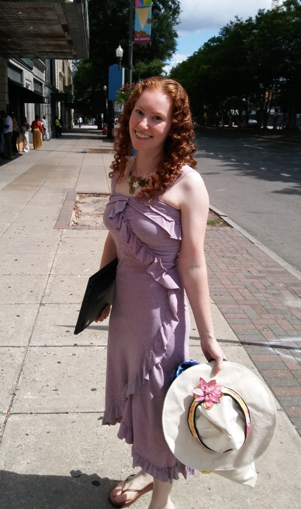 redhead in purple dress standing on sidewalk holding sun hat