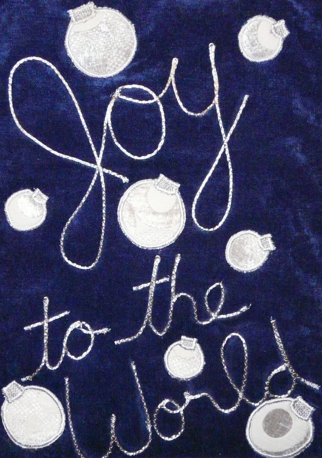 blue velvet wall hanging with couched silver text: Joy to the World