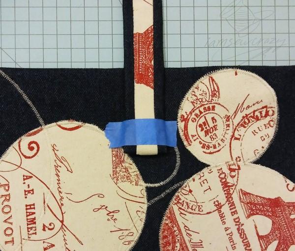 tape holding down handbag strap