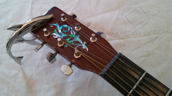 guitar neck with abalone decal and shark-shaped capo