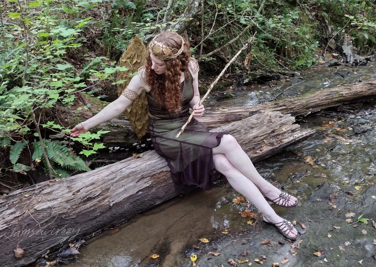 fairy sitting on fallen log in creek
