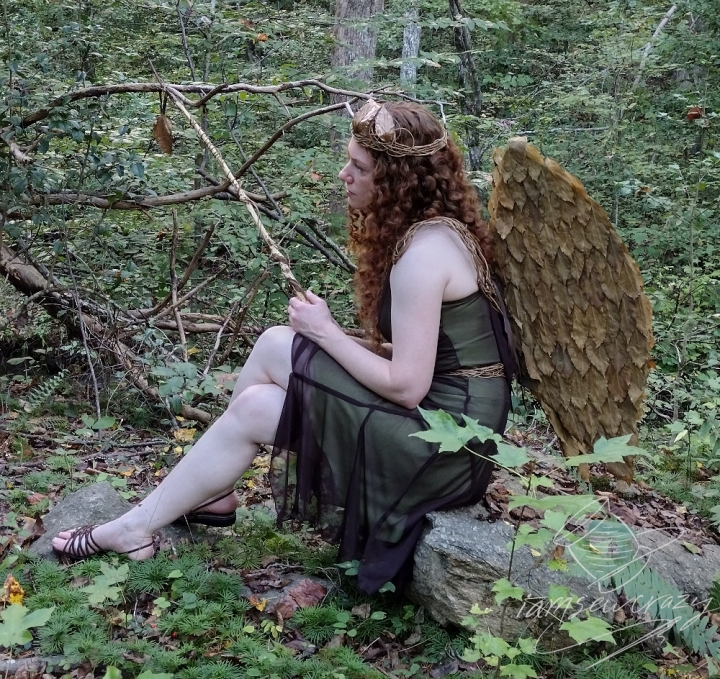 redhaired woman dressed as woodland fairy sitting on rock